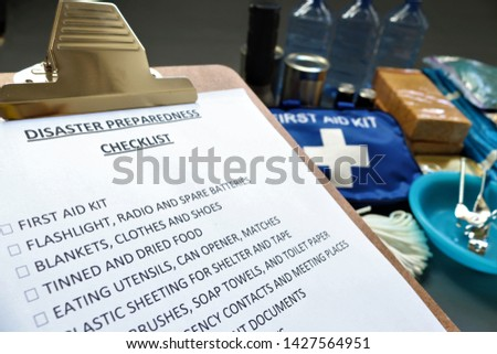 Disaster preparedness checklist on a clipboard with disaster relief items in the background.Such items would include a first aid kit,flashlight,tinned food,water,batteries and shelter. #1427564951