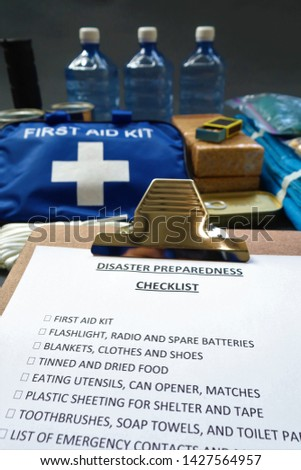 Disaster preparedness checklist on a clipboard with disaster relief items in the background.Such items would include a first aid kit,flashlight,tinned food,water,batteries and shelter. #1427564957
