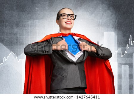 Happy business woman tearing off her shirt and transforming in super heroine. Smiling business lady with red hero cape on financial graph background. Brave super woman ready for new achievements. #1427645411