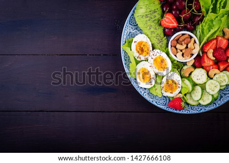 Plate with a paleo diet food. Boiled eggs, avocado, cucumber, nuts, cherry and strawberries. Paleo breakfast. Top view #1427666108