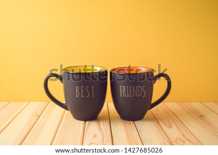 Chalkboard coffee mugs on wooden table with best friends text. Friendship day concept #1427685026