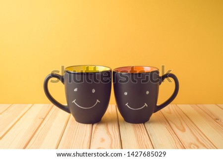 Chalkboard coffee mugs on wooden table with funny cute faces. Friendship day concept #1427685029