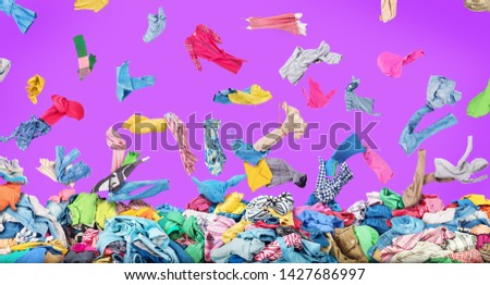 Sale concept. Separate clothing falling at the big pile of clothes on a purple background. Donation #1427686997