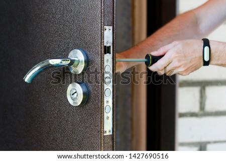 Handyman repair the door lock in metal entrance door, Man fixing lock with screwdriver, Close-up of repairing door, professional locksmith installing new deadbolt lock on house #1427690516