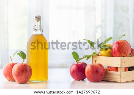 Healthy organic food. Apple cider vinegar in glass bottle and fresh red apples on a light background. #1427699672