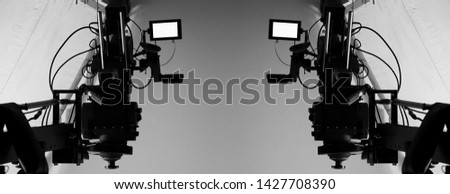4K high definition video camera monitor on tripod or crane in studio and softbox paper and professional lighting equipment for shooting or filming or broadcasting content to advertising commercial