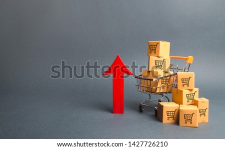 Shopping cart with cardboard boxes with a pattern of trading carts and a red up arrow. Growth wholesale and retail. Improving consumer sentiment, economic growth. Rising prices for goods, inflation #1427726210