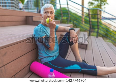 Beautiful sporty senior woman eating apple.  Beautiful senior sports lady smiling, holding an apple. Caucasian beautiful healthy athletic sportive senior woman eat green apple  #1427746904