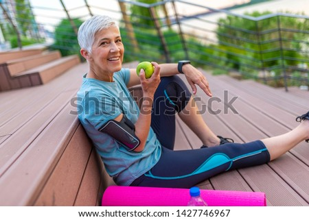 Sporty woman eating apple. Beautiful woman with gray hair in the early sixties relaxing after sport training. Healthy Age. Mature athletic woman eating an apple after sports training  #1427746967
