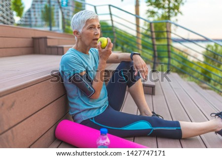 Senior woman with apple and water. Smiling woman eating green apple. Portrait of senior woman sitting on stairs after exercising. Sporty woman eating apple #1427747171
