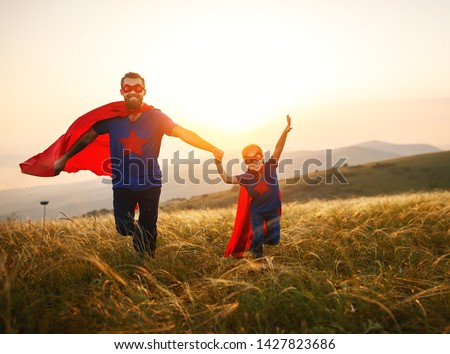 concept of father's day. dad and child daughter in hero superhero costume at sunset in nature #1427823686