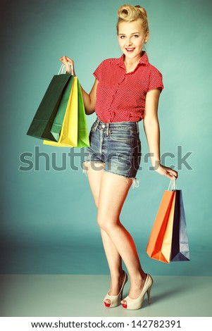 Retro style. Full length young woman in red dotted shirt and shorts with colourful shopping bags isolated on blue background #142782391