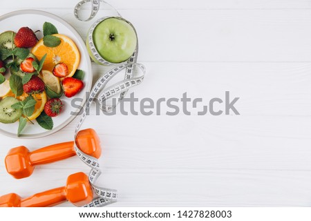Diet plan, menu or program, tape measure, water, dumbbells and diet food of fresh fruits on white background, weight loss and detox concept, top view #1427828003