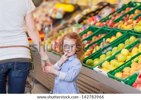 Image of a cute little girl roaming inside the supermarket with her mother #142783966