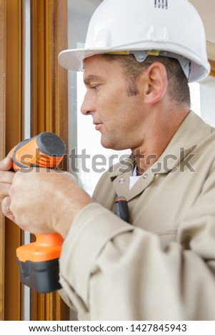 man drilling a hole in a window frame #1427845943