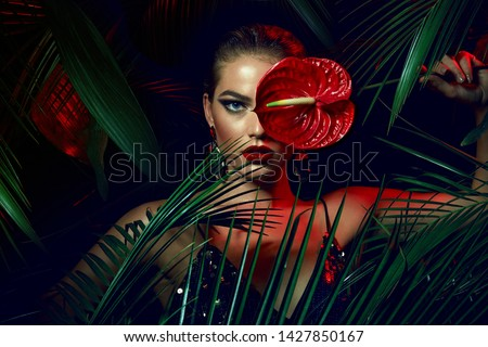 A beautiful tanned girl with natural make-up and wet hair stands in the jungle among exotic plants. #1427850167