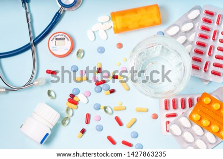 Colorful pills with glass of clear water over blue background. Medical pharmacy concept #1427863235