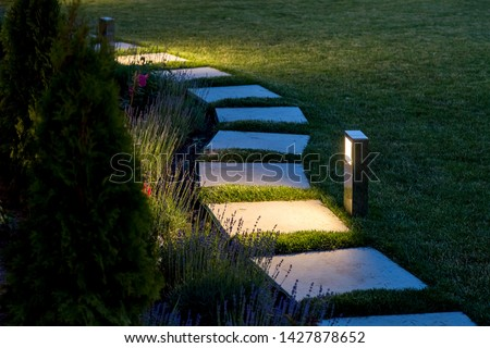 marble path of square tiles illuminated by a lantern glowing with a warm light in a backyard garden with a flower bed and a lawn copy space. #1427878652