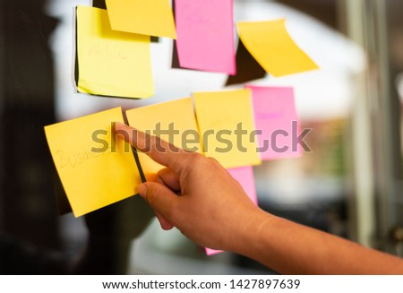 Close up business man hand pointing note sticky for brainstorm and share idea strategy workshop business.Brainstorming concept. #1427897639