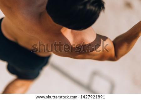 Handsome tired sportsman stretching on metal bars after hard workout #1427921891