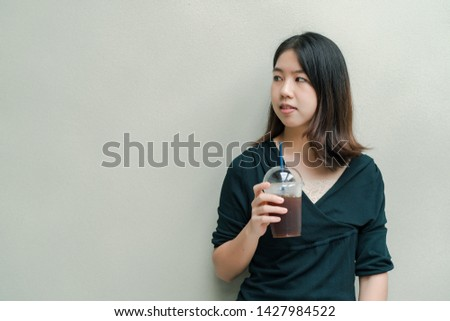 Asian beautiful woman Put on a black shirt, stand to drink cold coffee in the hand with pleasure #1427984522