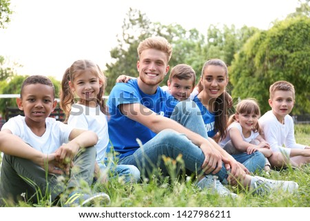 Volunteers and kids sitting on grass in park #1427986211