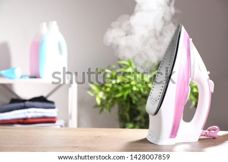 Modern iron with steam on table indoors. Space for text #1428007859