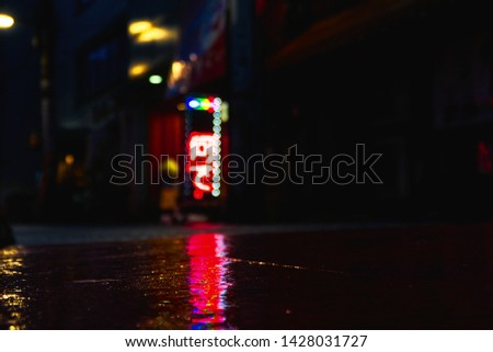 abstract picture of neon lights reflecting on wet asphalt in the nightlife of Tokyo. Picture with copy space. Rainy evening