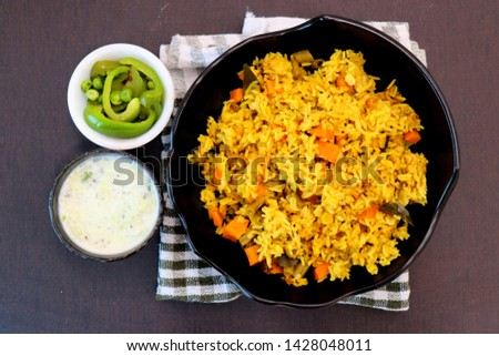 Indian Vegetable Pulav or Biryani made using Rice and vegetables like peas, carrots, beans. served with raita and saute peas, capsicum bowl.  #1428048011