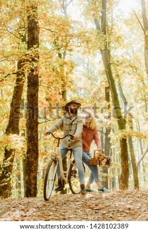 Couple in love ride bicycle together in forest park. Bearded man and woman relaxing in autumn forest. Romantic couple on date. Date and love. Autumn date hike in forest. Romantic date with bicycle. #1428102389