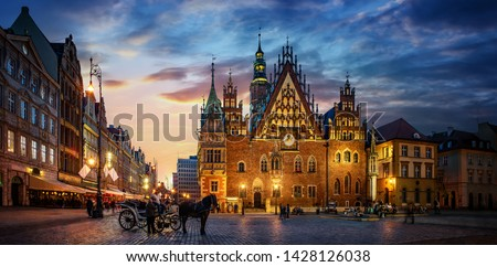 Wroclaw central market square with old houses, Town Hall and sunset, horse and carriage. Panoramic night view, long exposure.  Historical capital of Silesia, Wroclaw (Breslau) , Poland, Europe. #1428126038