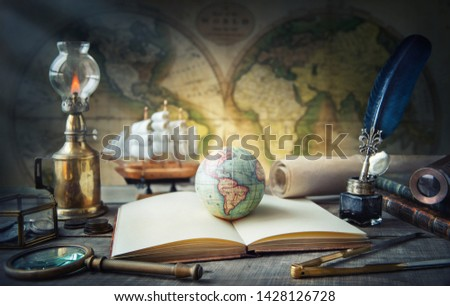 Exploration and nautical theme grunge background. Globe, telescope, divider, old coins, shell, map, book, hourglass, quill pen on wood desk. Columbus Day.  #1428126728