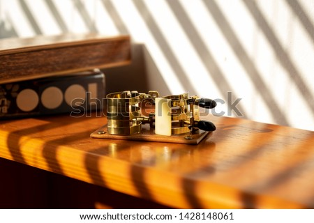 Saxophone ligatures are on the wood table. Beautiful shafts of bright sunlights are flooding into the room. Every color of shades, lights, wooden table, ligatures are in good harmony. #1428148061