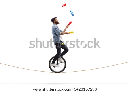 Full length profile shot of a male juggler with clubs riding a unicycle on a rope isolated on white background #1428157298