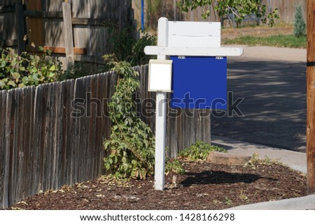 Blank isolated blue and white clipping path - real estate sign For Sale Lease - Home Property House in front of yard fence on street corner