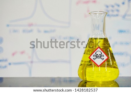 Erlenmeyer flask with Yellow liquid and chemical hazard warning symbols labels (acute toxicity symbol) on whiteboard with chemical learning background.