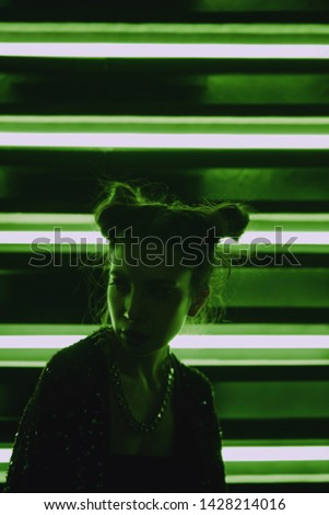 Cyberpunk style portrait of girl in futuristic green bathrobe with glitter. She poses against wall of neon lamps. Set is lit with green light. Clothes is oversized. Picture has dark noir tones.