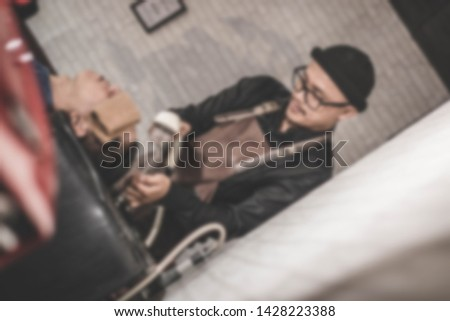 blurry portrait of barber washing costumer hair with stream water shower who relaxed in the chair sink with fresh towel inside vintage barbershop #1428223388