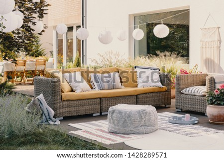 Pouf next to rattan couch and armchair on wooden terrace with flowers and lamps #1428289571
