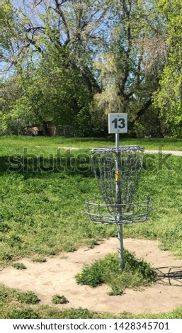 A disc golf basket, also known as a catcher or goal, composed of steel tubes, chains, and bar, on a course somewhere in the United States.  #1428345701