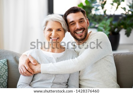 family, generation and people concept - happy smiling senior mother with adult son hugging at home #1428376460