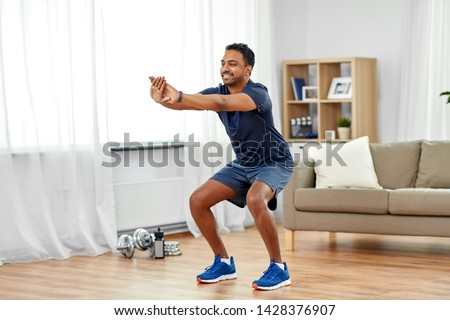 sport and healthy lifestyle concept - smiling indian man with fitness tracker exercising and doing squats at home #1428376907