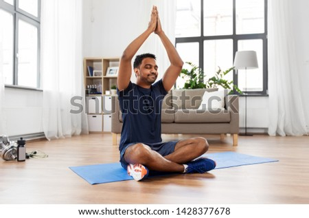 fitness, meditation and healthy lifestyle concept - indian man meditating in lotus pose on exercise mat at home #1428377678