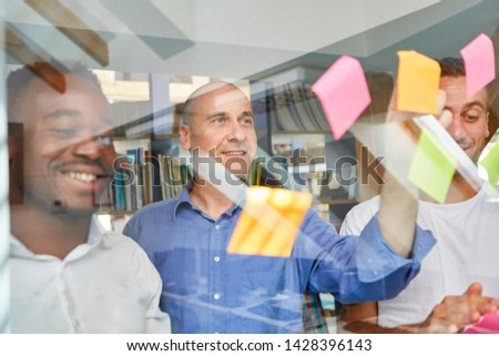 Creative business team collects project ideas on sticky notes in brainstorming workshop #1428396143