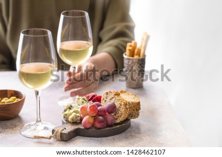 Woman holding glass of white wine in the restaurant. Different snacks, Blue cheese, olives, baguette slices and cured meat. Tasting party lifestylebackground. #1428462107