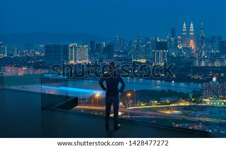 Businessman standing on open roof top balcony watching city night view . Business ambition and vision concept . #1428477272