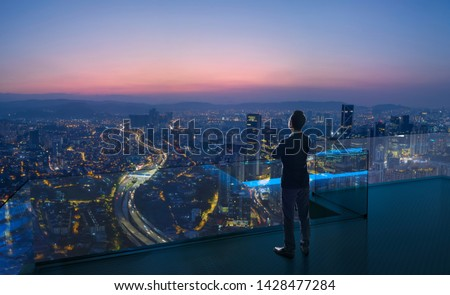 Businessman standing on open roof top balcony watching city night view . Business ambition and vision concept . #1428477284