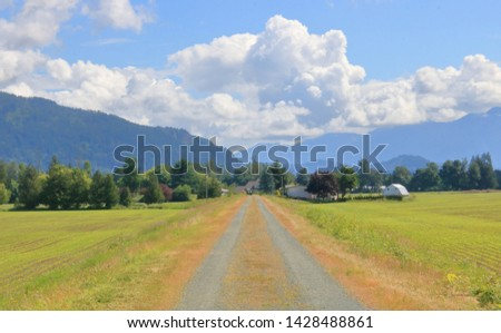 A wide elevated nature path leads to rolling countryside crowned by large cumulus clouds.  #1428488861