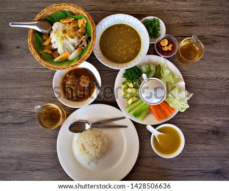 A set of myanmar dish (Burmese food) on the wooden table. Dishes are Myanmar(Burmese) style noodle (MonHinGa), Myanmar chicken curry and shrimp paste with soup #1428506636