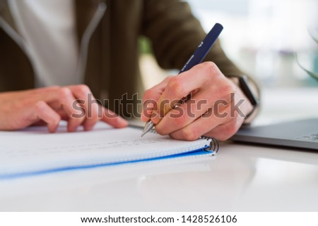 Close up of man hands writing on notebook, working taking notes #1428526106